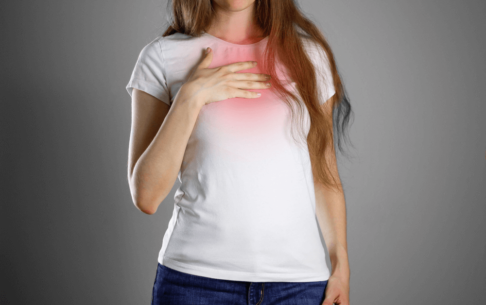 A women suffering from chest tightness, a common symptom for asthma and bronchiectasis
