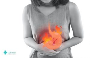 A woman suffering from heartburn as a result of eating spicy meals